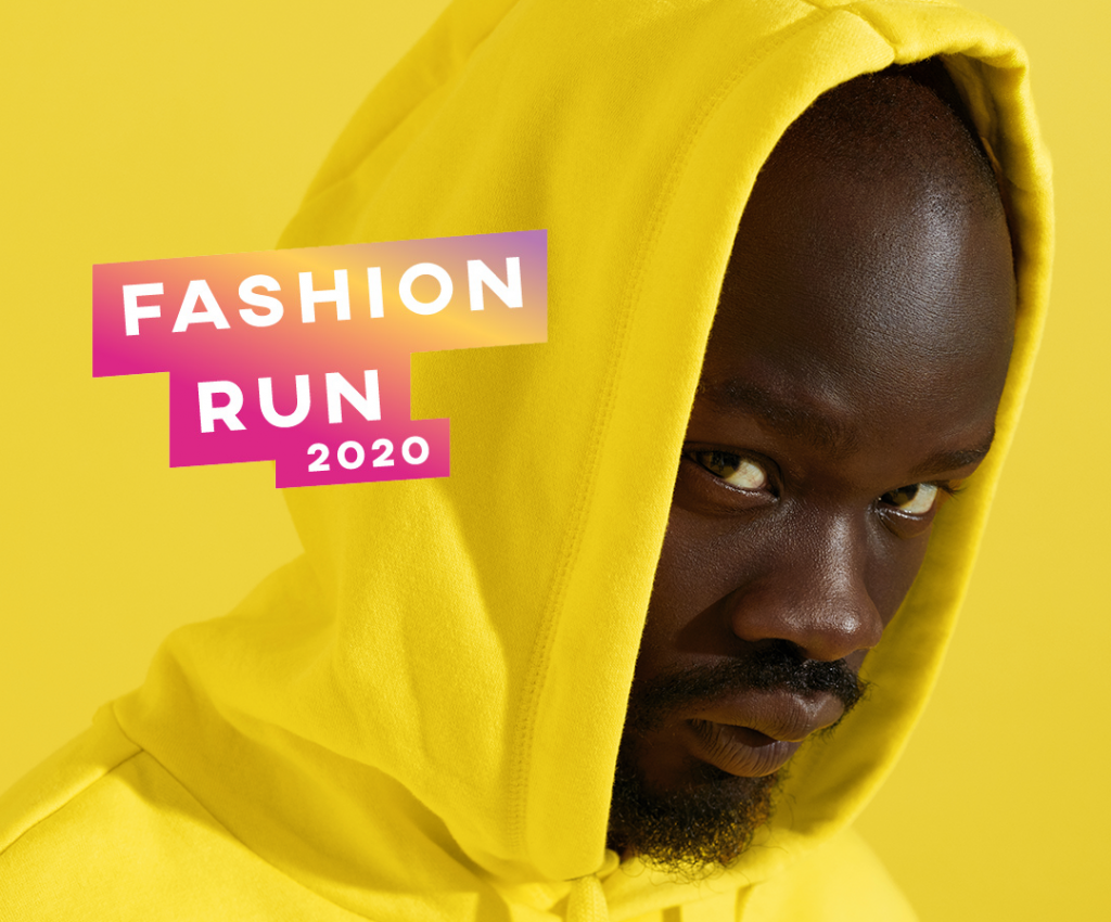 """A man, in a yellow hoodie on a yellow background, with the words """"Fashion run 2020"""""""