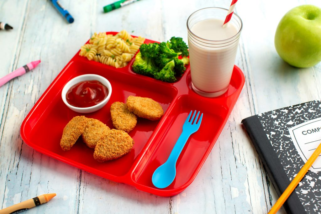 A plastic tray of food, including nuggets and vegetables.