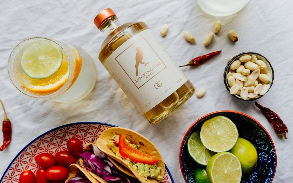 A bottle of Mockingbird Spirit, surrounded by slices of Lime and Orange.