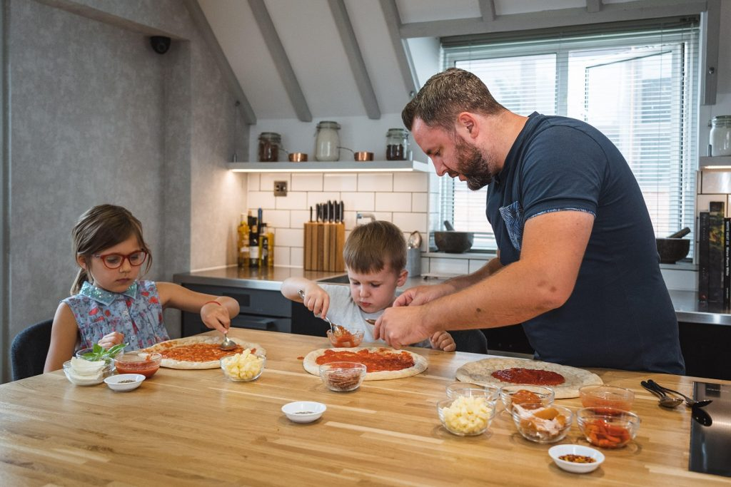 A family making pizza at home with a pizza kit